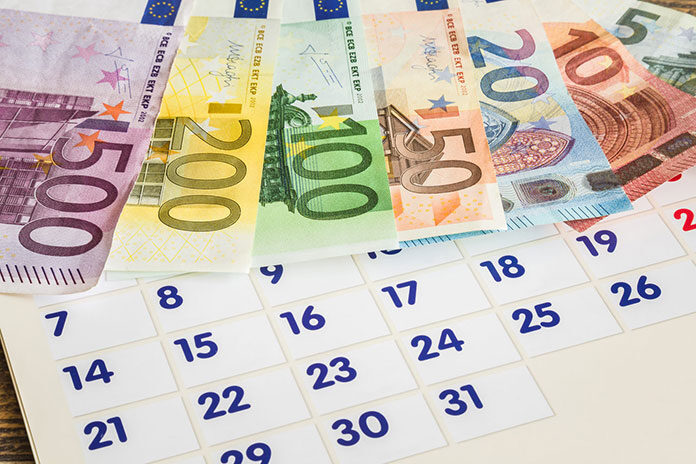 Kartka z kalendarza i pieniądze jako symbol kalendarza makroekonomicznego